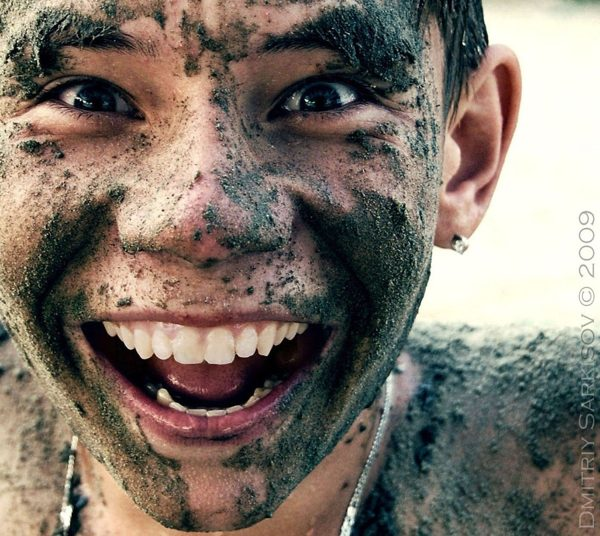 kid smiling and happy playing in mud